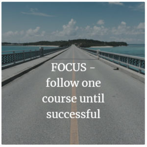 This is a road with the words Focus follow one course until successful written on it